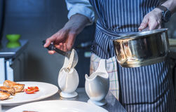 Chef finishing his plate and almost ready to serve. At the table Stock Image
