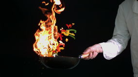 Chef flambeing peppers in wok. In slow motion stock footage