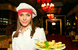 Chef with food. Young attractive female chef with dishes Royalty Free Stock Photo
