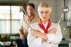 Chef - Frau - bei der Gaststättekücheaufstellung Stockfoto