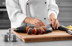 Chef with fresh cut salmon. In kitchen Royalty Free Stock Image