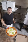 Chef with fresh take out pizza. Pizza chef taking hot pizza out of the oven Royalty Free Stock Photography