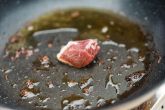 Chef Fried Marinated Diced Raw Beef in Pan with Rosemary Oil Stock Photo