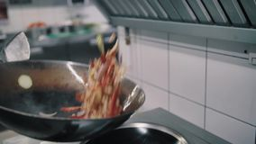 Chef fries food in a wok pan