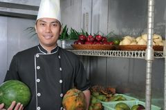 Chef in fruit storage. Chef in fruits storage holding papaya and watermelon Stock Photos