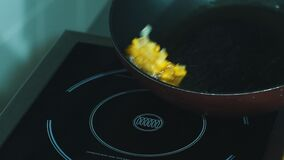 Chef fry corn in a pan. Frying vegetables on pan by chef slow motion, close up stock video