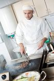 Chef frying beef steak on grill Royalty Free Stock Photography