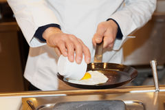 Chef is frying eggs on pan Stock Photography