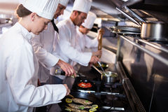 Chef frying fish in a frying pan Royalty Free Stock Images