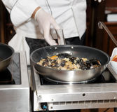 Chef frying mussels Royalty Free Stock Images
