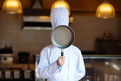 Chef with frying pan. Head chef covering face with a frying pan Royalty Free Stock Image