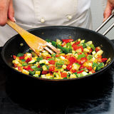 Chef frying peppers Stock Images