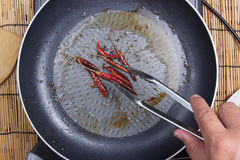 Chef frying red dried chlli in the pan Royalty Free Stock Photography