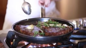 Chef frying rib eye steaks with butter garlic and rosemary in non stick pan stock video