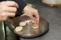 Chef is frying scallops on pan Royalty Free Stock Photo