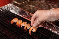 Chef is frying shrimps on an electric grill Royalty Free Stock Image