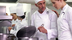 Chef frying vegetables then checking on colleague Stock Images
