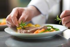 Chef garnishing a dish royalty free stock photo