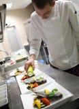 Chef garnishing in the kitchen garnishing Royalty Free Stock Image