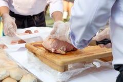 Chef geschnittener Schweinefleischausschnitt auf hölzernem Brett Lizenzfreies Stockbild