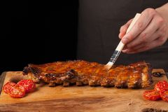 The chef gets BBQ sauce on ready-to-eat pork ribs lying on an old wooden table. A man prepares a snack to beer on a. Black background with copy space Stock Photos