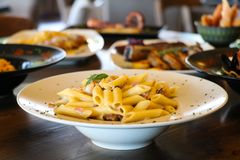 Chef gießt Olivenöl über frischem Salat in der Gaststätteküche Teigwaren penne auf weißer Platte Unschärfeplatten mit Nahrungsmit lizenzfreie stockfotografie