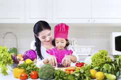 Chef girl learn to cut. Chef girl is learning how to cut vegetables with mom in the kitchen royalty free stock image