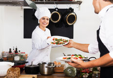 Chef giving salad to waitress. Cheerful female cook in uniform standing on kitchen and giving fresh green salad to waitress Royalty Free Stock Photography
