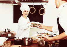 Chef giving salad to waitress. Cheerful female cook in uniform standing on kitchen and giving fresh green salad to waitress Royalty Free Stock Images