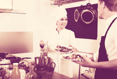 Chef giving salad to waitress. Glad female cook in uniform standing on kitchen and giving fresh green salad to waitress Stock Images