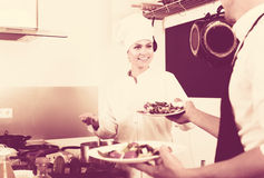 Chef giving salad to waitress. Smiling female cook in uniform standing on kitchen and giving fresh green salad to waitress Stock Photography