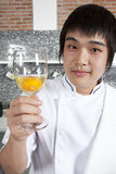 Chef and a glass of raw egg. Asian young chef holding a glass of raw egg Stock Photo