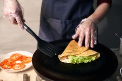 Chef making stuffed crepe, roll up crepe on hot cooktop. Traditional restaurant cooking concept. Detailed. Front view. royalty free stock photos