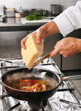 Chef grate cheese. In pan on professional kitchen stock image