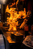 chef grilling bbq with flame of burning in restaurant Royalty Free Stock Photos