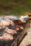 Chef grilling pork steak on flame. At the park Royalty Free Stock Image