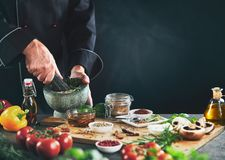 Chef grinding herbs next to seasoning containers royalty free stock photo
