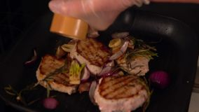 Chef grinding pepper on grilling pork medallions stock footage