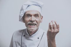 Chef With Hand in Foreground. Looking at Camera. Male Cooker. Kitchen Uniform. Isolated Grey Background. Closeup Portrait Photo. Old Man on Uniform. Emotional royalty free stock image
