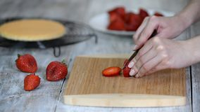 Chef Hand and Knife Slicing Fresh strawberry on wooden cutting board. Chef Hand and Knife Slicing Fresh strawberry on wooden cutting board stock video footage