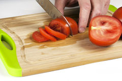 Chef Hand and Knife Slicing Tomato Stock Image