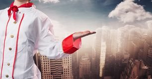 Chef with hand out at side against blurry skyline Royalty Free Stock Photography