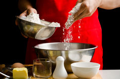 Chef hand poring flour in a bowl Royalty Free Stock Photos