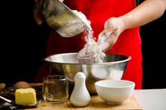 Chef hand poring flour in a bowl Royalty Free Stock Images