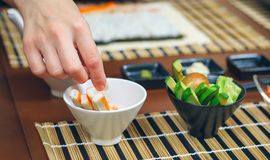 Chef hand picking up a crab stick to make sushi stock photo