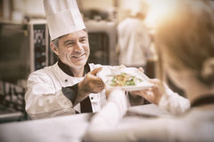 Chef handing dinner dish to waitress at order station. Happy chef handing dinner dish to waitress in kitchen at order station Royalty Free Stock Image