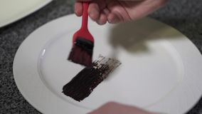 Chef hands applying thick sause on the plate using red rubber brush close up in the modern restaurant. Cook decorating stock footage