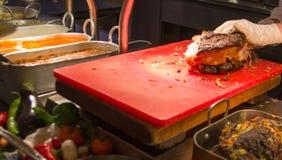 Chef-Hands-Ausschnitt grillte Ersatzrindfleisch auf einem Schreibtisch Stockfoto