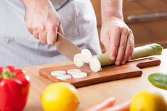 Chef hands cutting leek in kitchen Stock Image