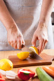 Chef hands cutting lemon in kitchen Royalty Free Stock Photography